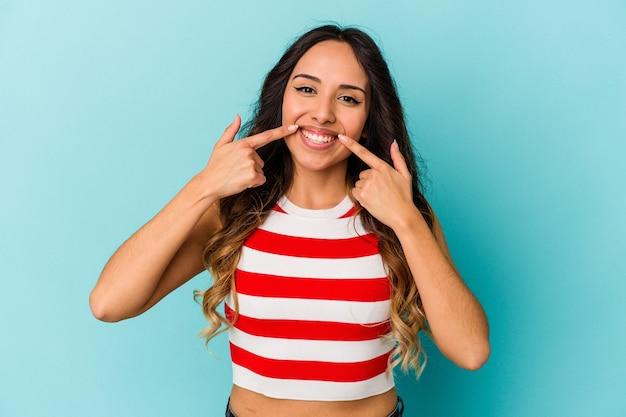 입에서 손가락을 가리키는 파란색 벽 미소에 고립 된 젊은 멕시코 여자.