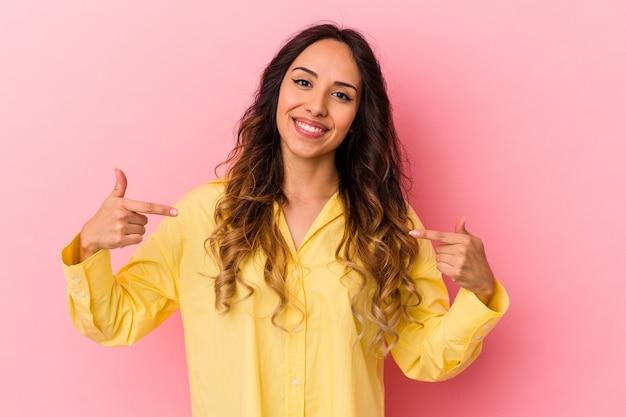 분홍색 배경에 고립 된 젊은 멕시코 여자는 손가락, 긍정적 인 느낌으로 아래로 가리 킵니다.