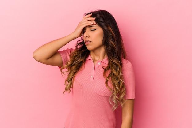Молодая мексиканская женщина изолирована на розовом фоне, трогательно висков и имея головную боль.