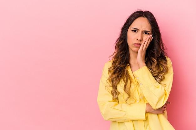 Молодая мексиканская женщина изолирована на розовой стене, которая чувствует себя грустной и задумчивой, глядя на пространство для копирования.