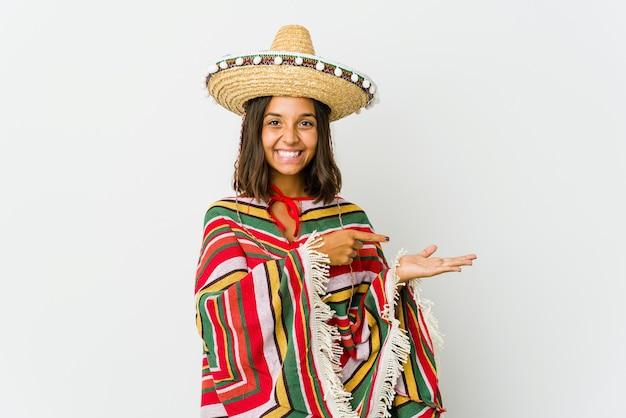Молодая мексиканская женщина, изолированных на белом фоне, взволнована, держа копию пространства на ладони.