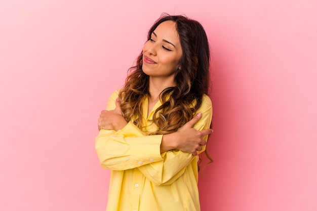 Young mexican woman isolated on pink wall hugs, smiling carefree and happy.