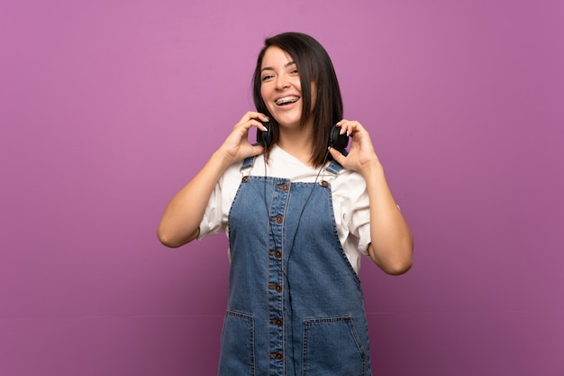 Young mexican woman over isolated wall listening to music with headphones