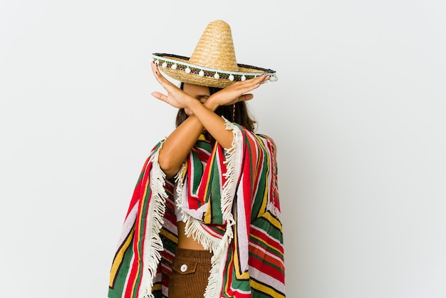 Young mexican woman isolated on white wall keeping two arms crossed, denial concept.