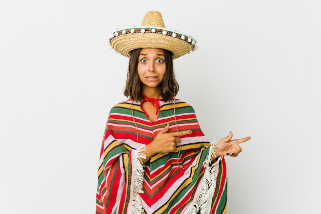 Young mexican woman isolated on white wall shocked pointing with index fingers to a copy space.
