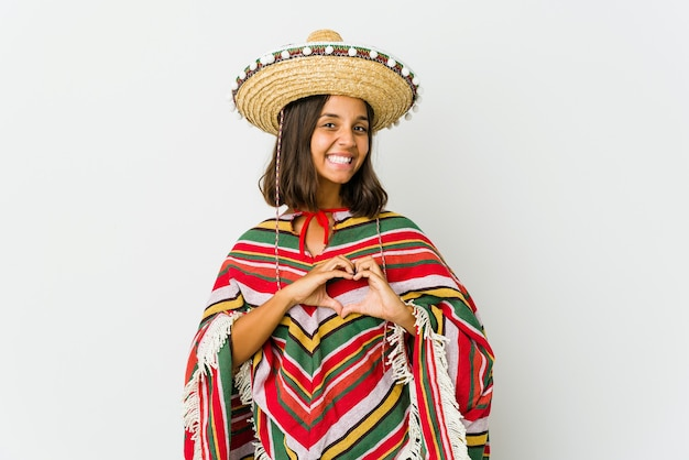 Young mexican woman isolated on white wall smiling and showing a heart shape with hands.