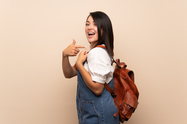 Young mexican woman over isolated with backpack