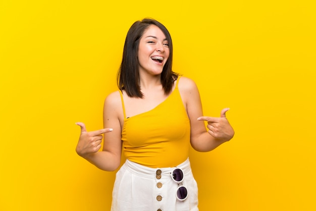 Young mexican woman over isolated yellow background proud and self-satisfied
