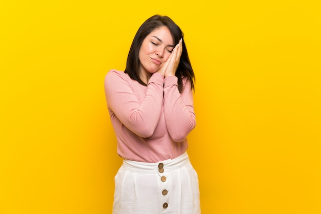 Young mexican woman over isolated yellow  making sleep gesture in dorable expression