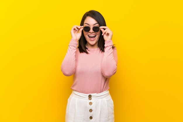 Young mexican woman over isolated yellow  with glasses and surprised