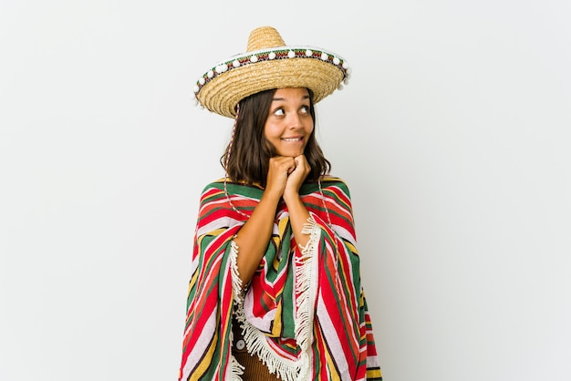Young mexican woman keeps hands under chin, is looking happily aside.