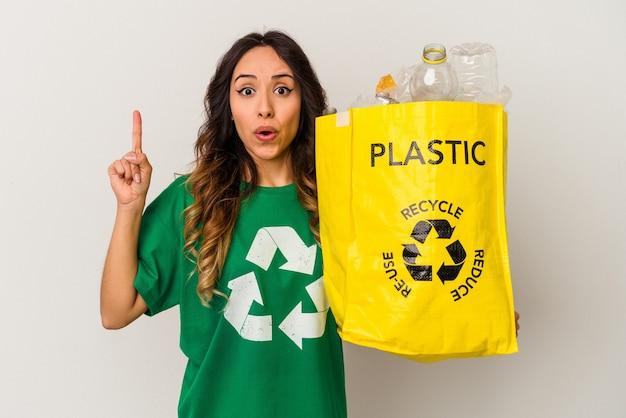 いくつかの素晴らしいアイデア、創造性の概念を持っている白い背景で隔離のプラスチックをリサイクルする若いメキシコ人女性。
