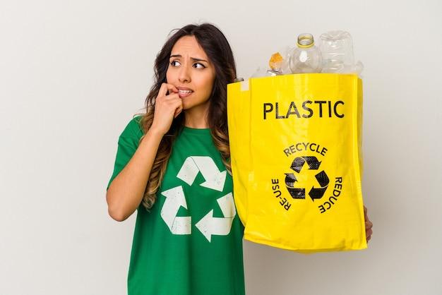 白い背景で隔離のプラスチックをリサイクルする若いメキシコ人女性は、コピースペースを見ている何かについて考えてリラックスしました。