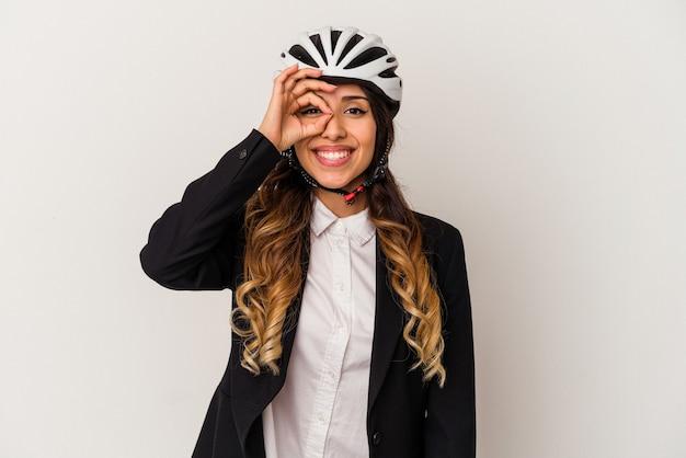 흰색 배경에 고립 된 작업을 자전거를 타고 젊은 멕시코 여자 눈에 확인 제스처를 유지 흥분.
