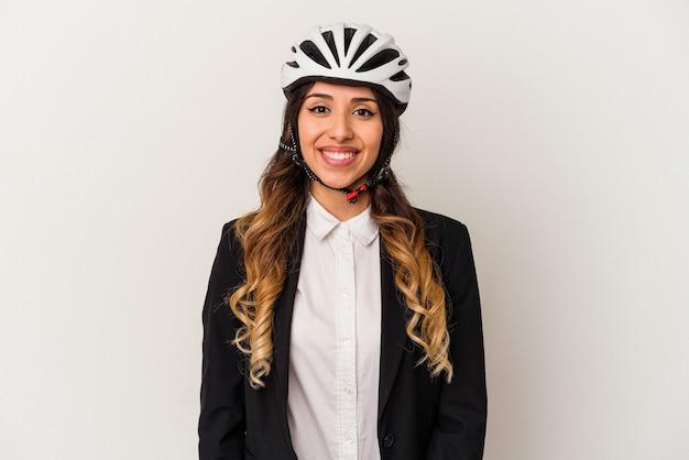 自転車に乗って仕事をする若いメキシコ人女性は、幸せ、笑顔、陽気な白い背景で隔離。