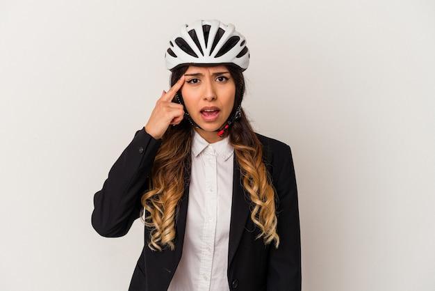 人差し指で失望のジェスチャーを示す白い背景に隔離された仕事に自転車に乗る若いメキシコ人女性。