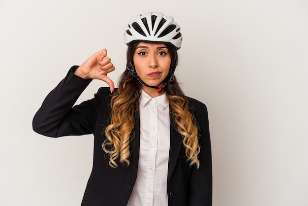 自転車に乗って仕事をする若いメキシコ人女性は、白い背景に孤立し、嫌なジェスチャーを示し、親指を下に向けます。不一致の概念。