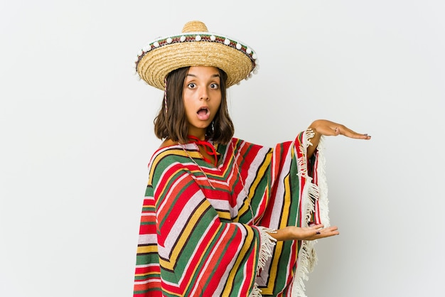 Young mexican woman shocked and amazed holding a copy space between hands.