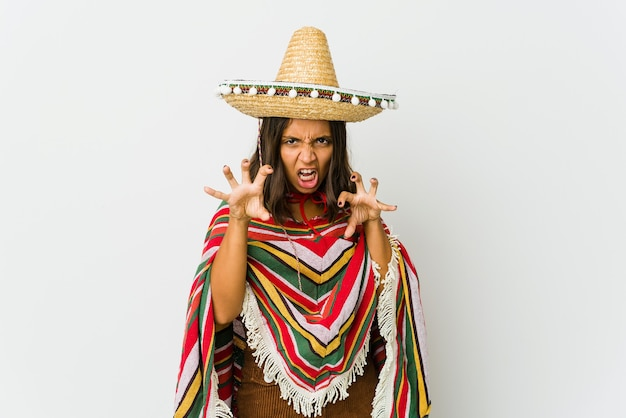 Young mexican woman showing claws imitating a cat, aggressive gesture.