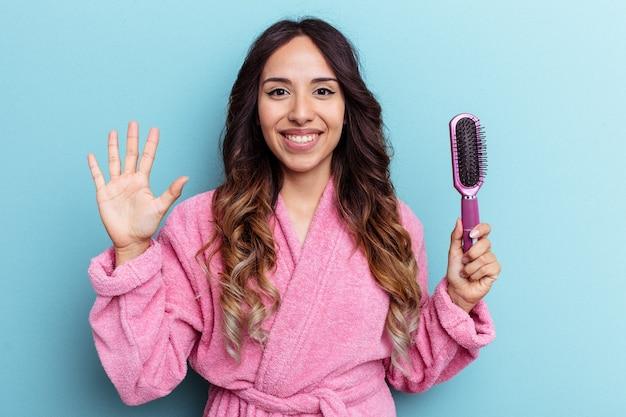 青い背景に分離されたブラシを保持しているバスローブを着ている若いメキシコ人女性は、指で5番を示して陽気に笑っています。