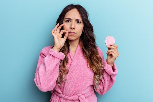 Молодая мексиканская женщина в халате держит губку для снятия макияжа, изолированную на синем фоне с пальцами на губах, храня в секрете.