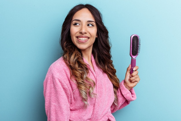 Young mexican woman wearing a bathrobe holding a brush isolated on blue background looks aside smiling, cheerful and pleasant.