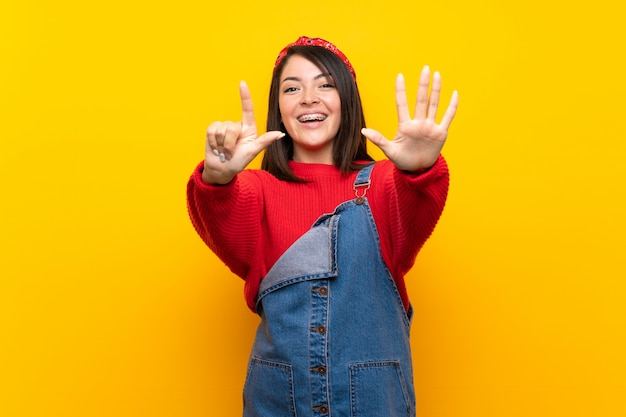 Young mexican woman with overalls over yellow wall counting seven with fingers