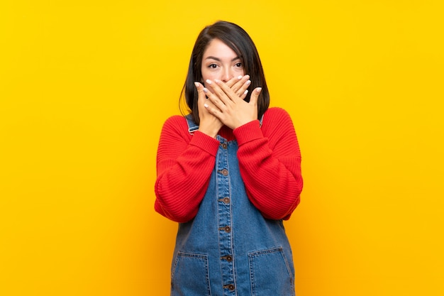 Young mexican woman with overalls over yellow wall covering mouth with hands