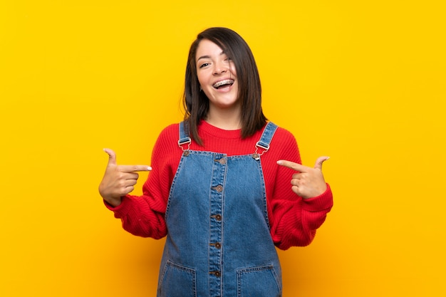 Young mexican woman with overalls over yellow wall proud and self-satisfied