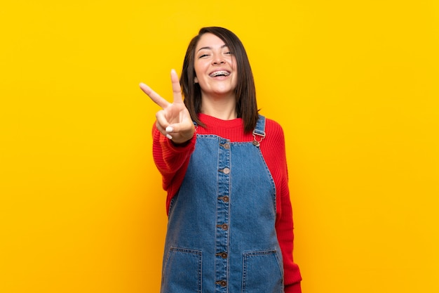 Young mexican woman with overalls over yellow wall smiling and showing victory sign