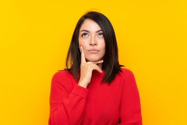 Young mexican woman with red sweater over yellow wall thinking an idea
