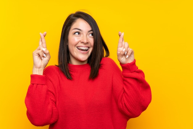 Young mexican woman with red sweater over yellow wall with fingers crossing