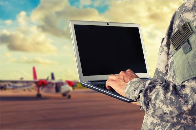 배경에 노트북과 젊은 군인 남자 초상화