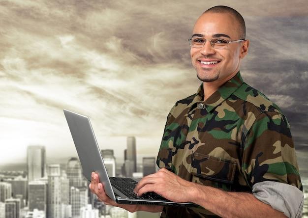 背景にラップトップを持つ若い軍の兵士の男の肖像画