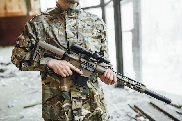 A young military soldier patrols a building with a big rifle.