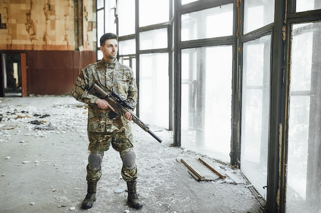 A young military soldier patrols a building with a big rifle