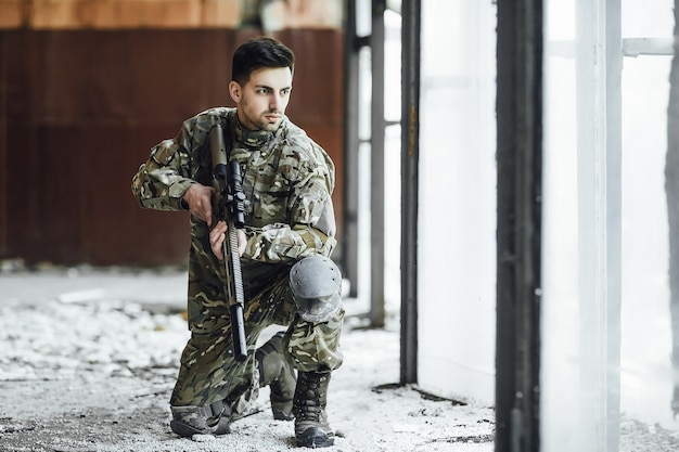 A young military soldier sits with a big rifle in his hands, near the window of a collapsed building