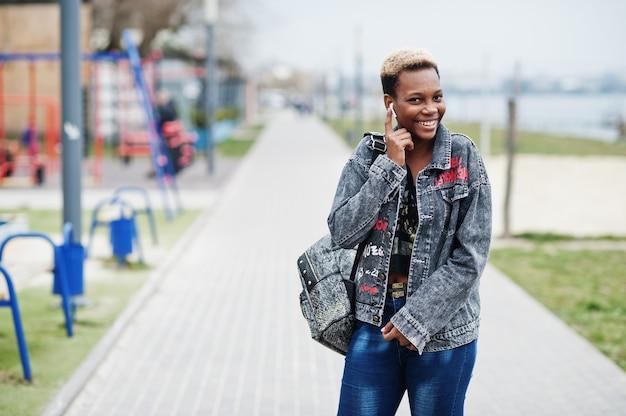 市内の若いミレニアル世代のアフリカ系アメリカ人の女の子。ワイヤレスイヤホンで幸せな黒人女性。 z世代のコンセプト。