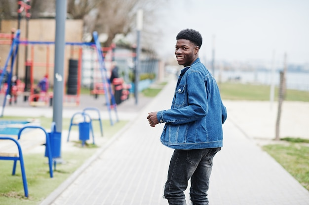 Young millennial african boy in city. happy black man in jeans jacket. generation z concept.