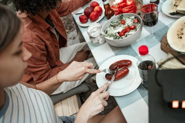 テーブルに座って、グランピングでグリルソーセージを食べるミレニアル世代の少女。電球のライトの下で野外ピクニックでキャンプする幸せなミレニアル世代。アウトドアで友達と過ごす時間、バーベキューパーティー