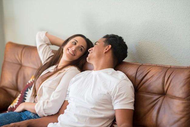 若いミレニアル世代の異人種間のカップルは、黒人の男の子と白人の女の子が一緒に立って笑顔でお互いの生活と家の概念を見てリビングルームの関係で自宅で愛を抱きしめます
