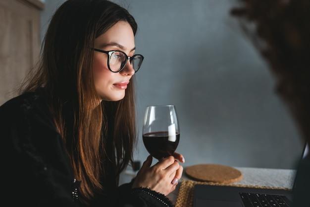 랩톱 컴퓨터에서 화상 통화를하고 와인을 마시는 젊은 밀레 니얼 여성, 친구 또는 가족과 의사 소통하기 위해 기술 사용