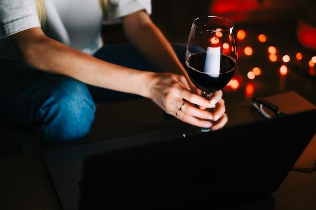 Молодая женщина из поколения миллениума, имеющая видеозвонок на портативном компьютере и пьющая вино, использует технологии для общения с друзьями или семьей.