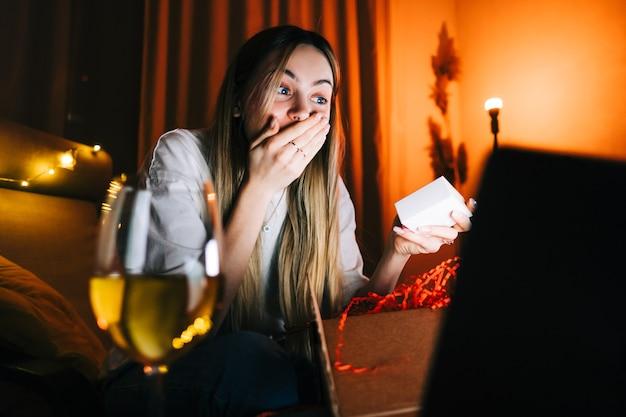 Молодая миллениальная женщина открывает подарок перед портативным компьютером во время видеозвонка и пьет вино, использует технологии для общения с друзьями или семьей.