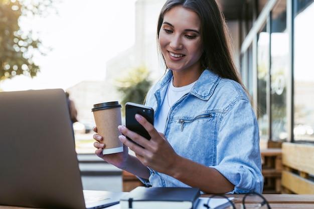 Молодая женщина тысячелетия работает в кафе на открытой террасе, сидя перед ноутбуком, разговаривает по телефону.