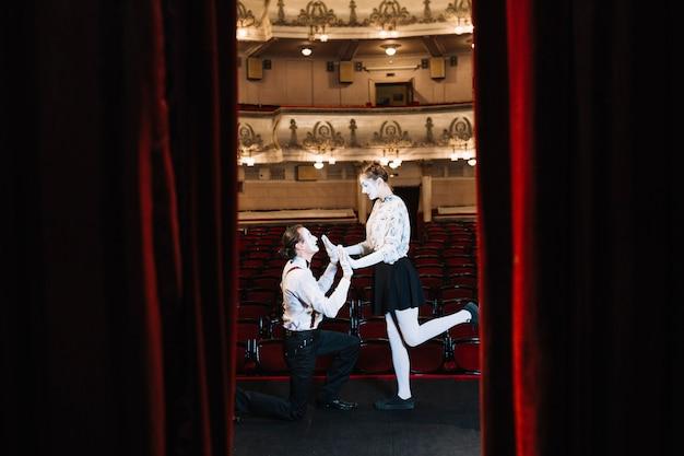 Молодая пара мим, выступающая на сцене, увиденная через открытый красный занавес