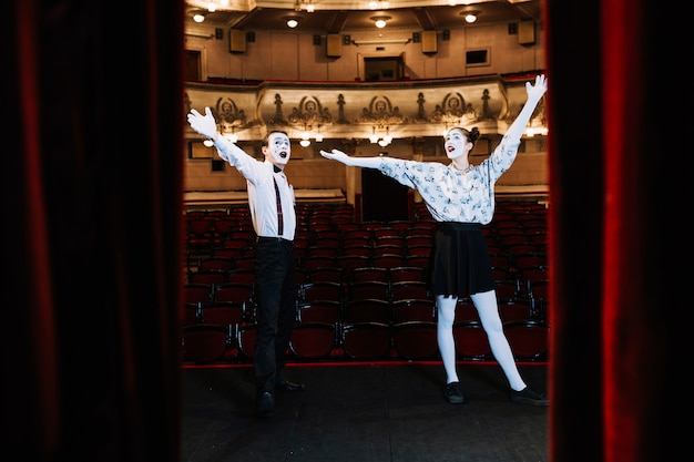 Young mime couple standing on stage raising their arms