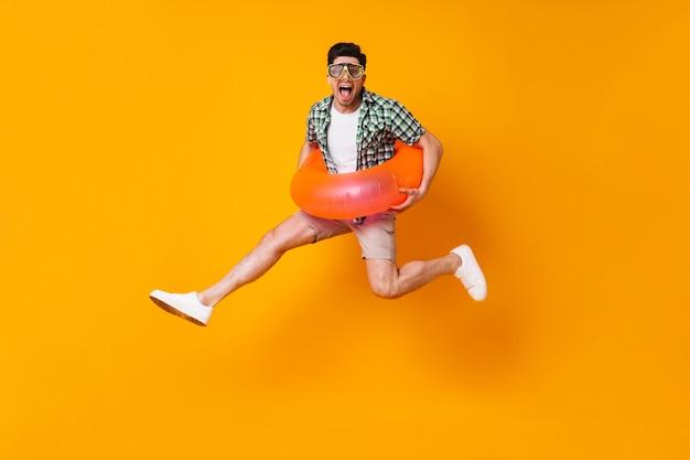 Giovane uomo dispettoso in abito estivo e maschera subacquea che salta con cerchio gonfiabile su spazio arancione.