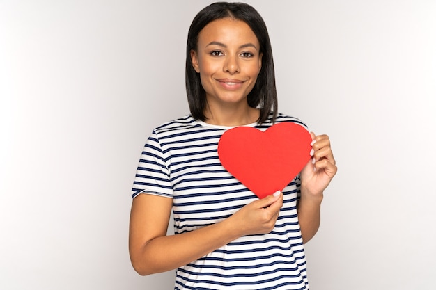 젊은 혼혈 여성은 발렌타인 데이 휴가 사랑과 로맨스를 위해 붉은 심장 모양의 엽서를 들고 있습니다.