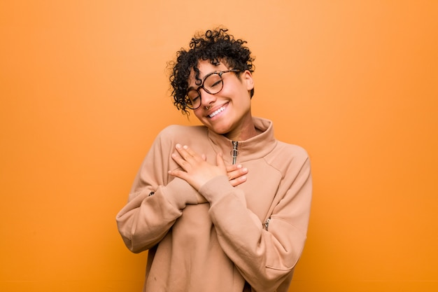 Young mixed african american woman against a brown background has friendly expression